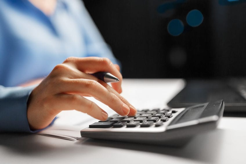 business, finance and accounting concept - close up of businesswoman with calculator counting and filling tax form at night office