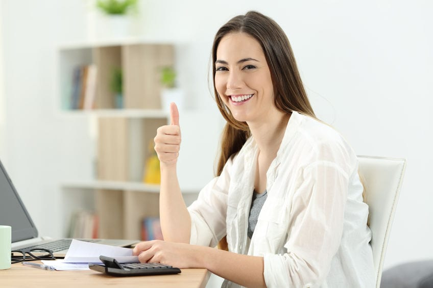 Happy woman doing acoounting looking at you at home