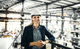 A portrait of a young industrial woman engineer standing in a factory.