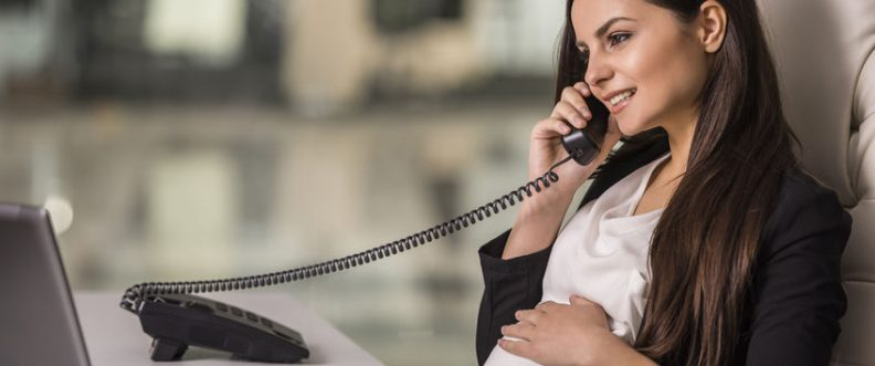 Pregnant adult businesswoman working with laptop and talking on phone in office.